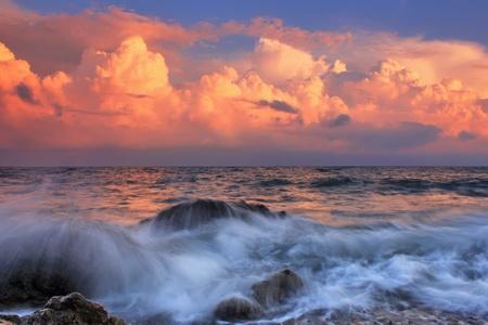 Stormy sunrise in ocean bay Standard-Bild