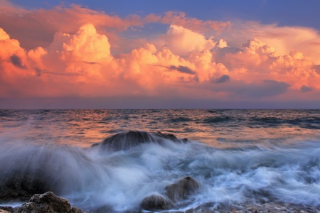 storm waves: Stormy sunrise in ocean bay Stock Photo