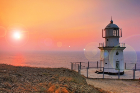 Lighthouse on the coast at dawn photo