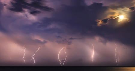 Severe thunderstorm over the ocean. Moonlight photo