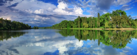 early summer: Panorama of cloudy sky reflection in the lake