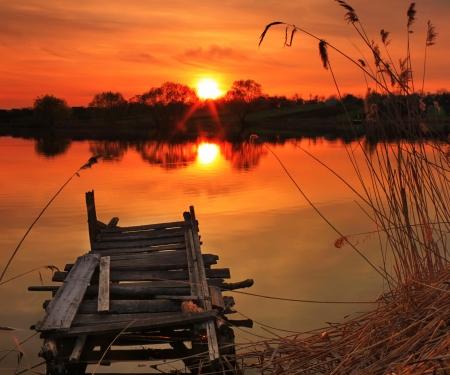 the boat on the river: Antiguo puente de pesca en el lago al atardecer