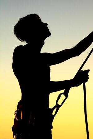 Silhouette insuring climber photo