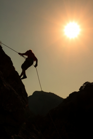 descending: Climber on sunset sky background