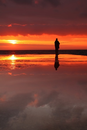 Fisherman at sunrise on the sea photo
