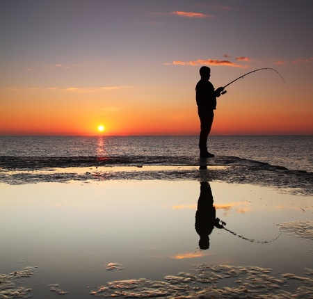 Fisherman at sunrise on the sea