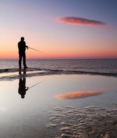 bass fishing: Fishermen at sunrise on the sea pier