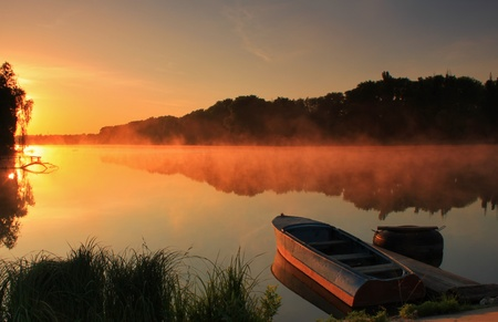 Boat on the misty river at sunrise Stock Photo