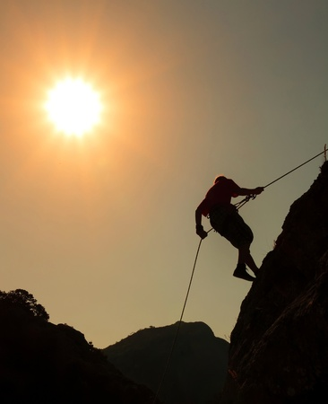 Climber on sunset sky background photo