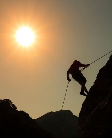 stijger: Klimmer op zonsondergang hemel achtergrond