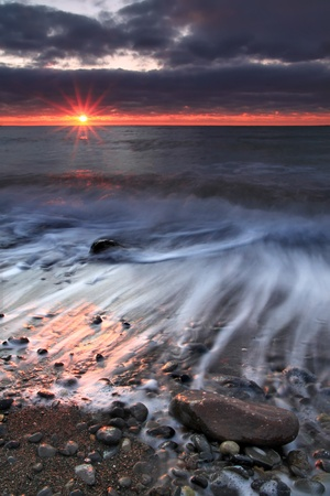 storm tide: Sunrise on the ocean beach