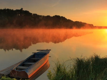 Boat on the shore of a misty lake on a summer morning  Stock Photo