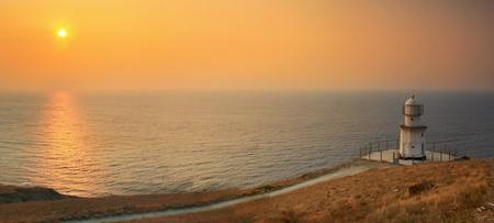 Lighthouse on the ocean beach at sunrise photo