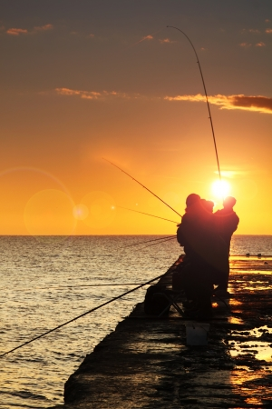 Silhouette of fishermen at sunrise photo