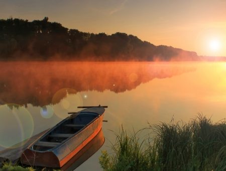 Boat on the shore of a misty lake on a summer morning  photo