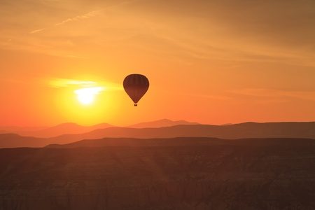 Hot air balloon is flying at sunrise  photo