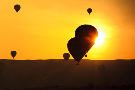 Silhouettes of balloons at sunset sky photo
