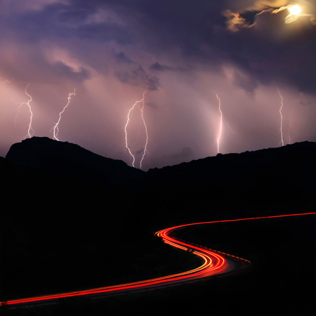 Night road in the mountains during a thunderstorm