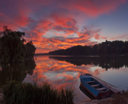 Panorama of beautiful dawn on lake with boat photo
