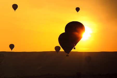 Silhouettes of balloons at sunset sky background photo