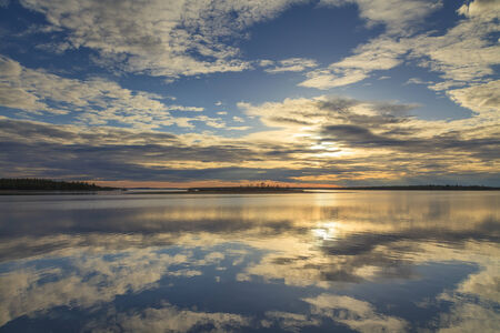 Cloudy sky reflected in the lake Stock Photo