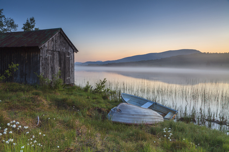View on foggy lake with boats on the shore. Norway.  photo