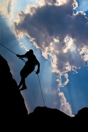abseiling: Climber on the mountain against the blue sky