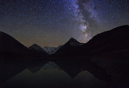 Magic night landscape with mountains, frozen lake and amazing starry sky. photo
