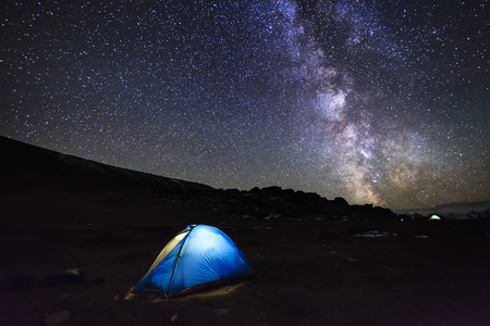 Tent with travelers in the mountains on the background of the magical starry sky. photo