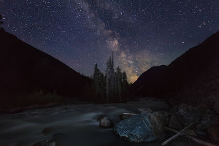 Magic night landscape with mountains, river and amazing starry sky. photo