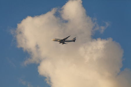 Flying plane against the blue sky and white clouds photo
