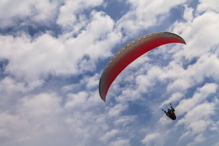 high flier: Flying paraglider on a background of blue sky and white clouds Stock Photo