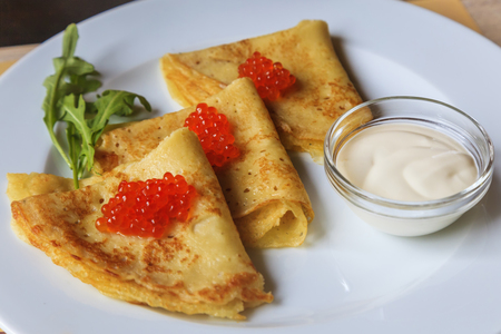 Delicious pancakes with red caviar and arugula on a white plate photo