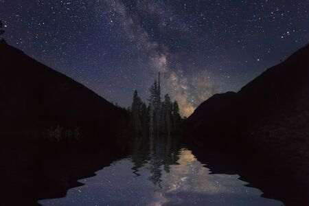 Amazing night landscape with mountains and stars. Reflection of the night sky in the lake. photo