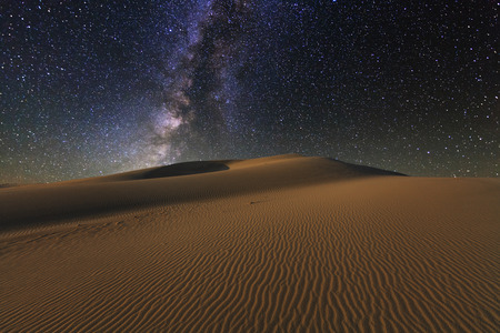 밤 별이 빛나는 하늘 아래 고비 사막의 놀라운 전망을 제공합니다.