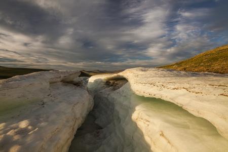 melting ice: Large pieces of melting ice on a stone beach.