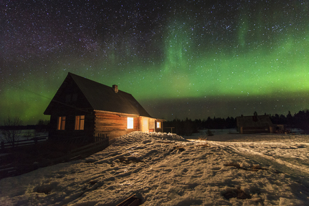 The wooden house on a background of starry sky and northern lights.