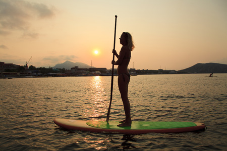 sup: Silhouette of a beautiful woman on Stand Up Paddle Board. SUP.