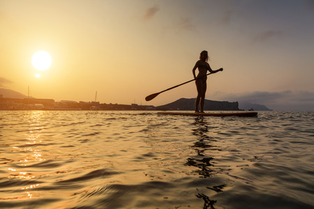 to stand: Silhouette of a beautiful woman on Stand Up Paddle Board. SUP.