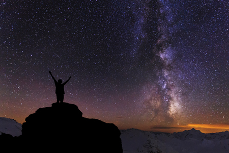 Silhouette of the person on the high rock at Milky Way background photo