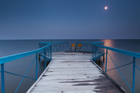 pierce: Pierce with two chairs against a nightscape. Stock Photo