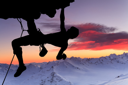 rappel: Silhouette of a rock climber on a rock against a beautiful sky.