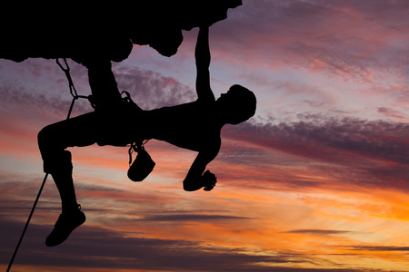 Silhouette of a rock climber on a rock against a beautiful sky. photo