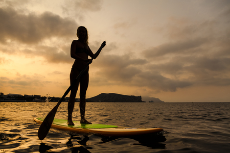 Silhouette of a beautiful woman on Stand Up Paddle Board. SUP.