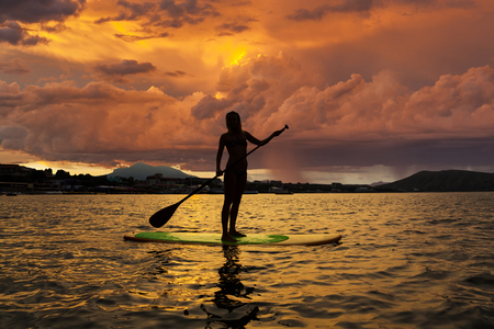 Silhouette of a girl on Stand Up Paddle Board on the background of stormy sky. SUP.