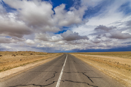 on the lonely road: Lonely road in the desert under a cloudy sky.