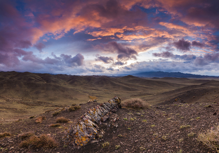 pastureland: Colorful sunset over the rocky steppe. Mongolia. Stock Photo