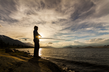 fishingpole: Silhouette of a fisherman with a fishing rod on the background of the river and mountains
