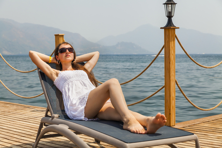 lounger: Slim young woman in a white sundress on a lounger.