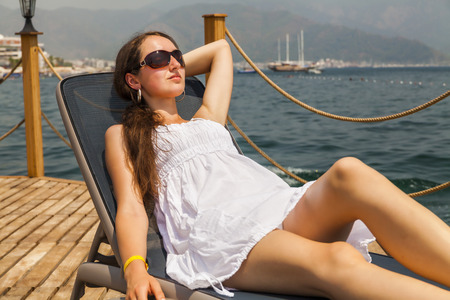 sundress: Slim young woman in a white sundress on a lounger.